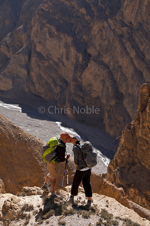 Trekkers Doug & Amy Hahn kiss on the cliffs above the Dhechyang Khola, a tributary of the Kali Gandaki River in Nepal's Upper Mustang Region.