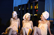 Three young women wrapped in towels gossiping in a SPA
