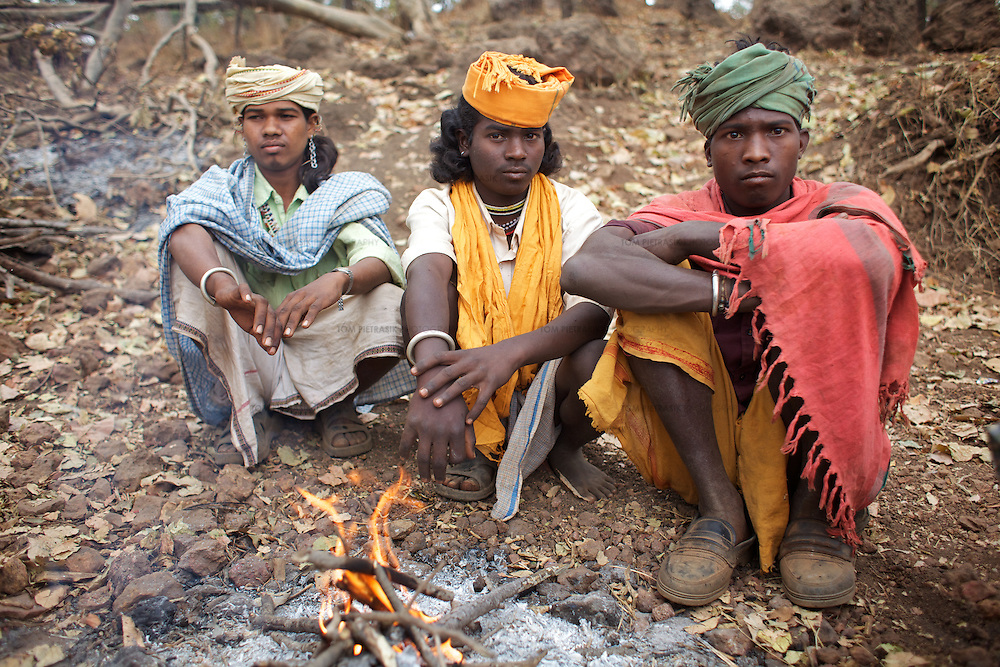 Adivasi (tribal) Baiga men from the village of Burbhus Pani wait on the road for truck drivers en route to the Bodhi Daldali Bauxite mine to hire them for casual mining work. Most of the trucks, which originate in Chhattisgarh capital city Raipur, are manned by teams of five workers but those that do not will recruit local Baigas for casual day work at a rate of Rs.125 per day (bauxite fetches Rs.600-700 per ton). The trucks ferry the bauxite to Raipur from where it is sent 600km by train for processing into aluminum in the state of Orissa. Located in the Maikal hill range, the 668 hectare Bodhi Bodhi Daldali mine, run by Balco &amp; Vedanta (Vedanta is a UK headquartered company), has been operational since 2003. Many Baiga families living on the site of the mine were relocated to make way for the mine. Enticed by compensation and often empty promises of employment and health and education services, most relocated people have regretted moving from their ancestral lands. The mine directly employs just 70 people. 750 contractors, most of them casual day-wage workers, provide the labour without which the mine would not function. <br /> <br /> Photo: Tom Pietrasik<br /> Kawardha District, Chhattisgarh. India<br /> February 20th 2011