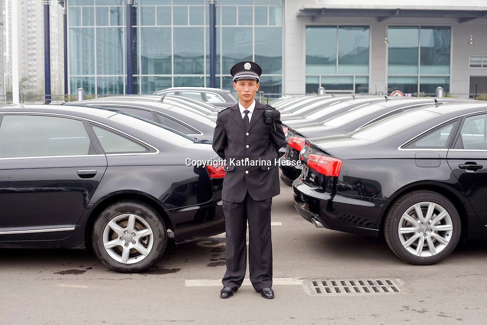 CHENGDU, 10/17/2012 :   ein Waechter gruesst und verabschiedet Kunden am Eingang von Audi New Elements in Chengdu.