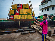 22 NOVEMBER 2017 - YANGON, MYANMAR: Workers load pallets of Burmese liquor onto a cargo ship taking the liquor up the Irrawaddy River. Myanmar's road system lags behind its neighbors in Southeast Asia and a lot of cargo is still moved by ships and barges.    PHOTO BY JACK KURTZ