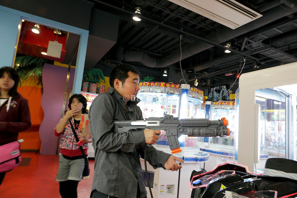 young adult boy playing with a shooting game inside a gaming arcade Japan