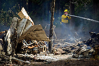 A Kootenai County firefighter sprays water along the edge of the fire that bordered a forested area.