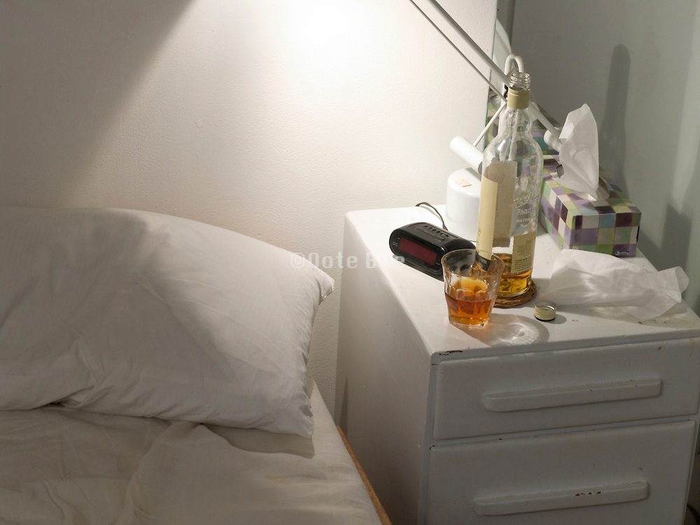 open whisky bottle with glass on a night stand by bed