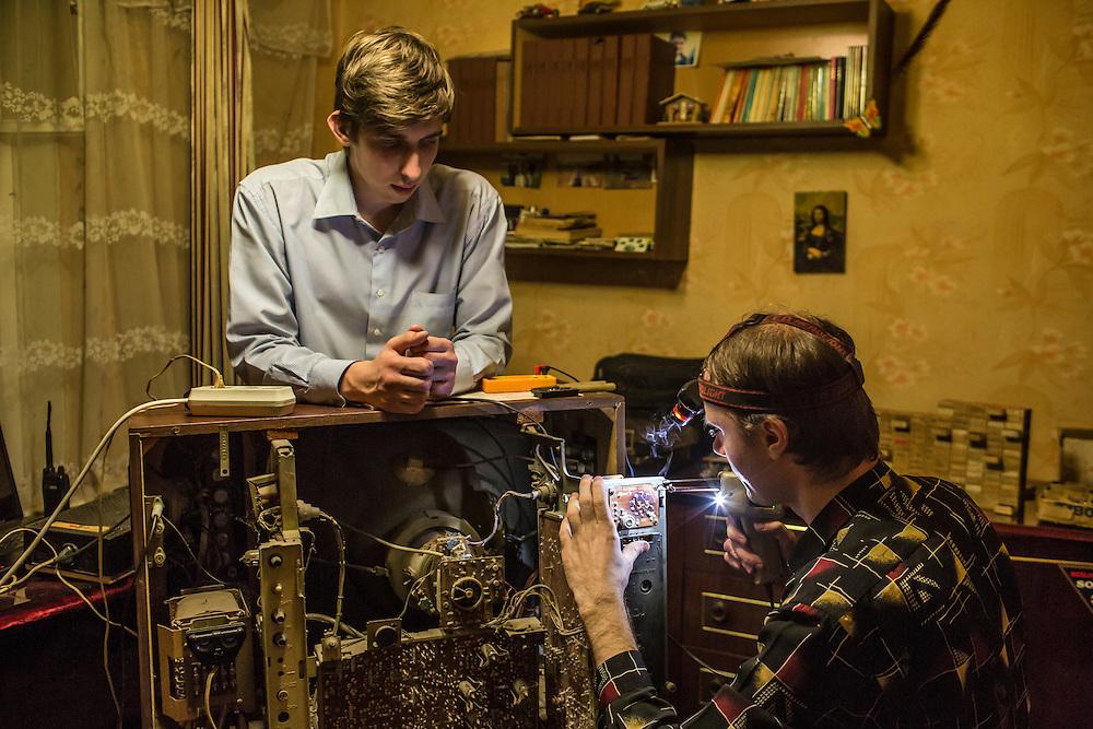 LUHANSK, UKRAINE - MARCH 15, 2015: Pavel Pavlov, left, watches as Aleksandr Kryukov repairs an old Soviet television in Luhansk, Ukraine. CREDIT: Brendan Hoffman for The New York Times