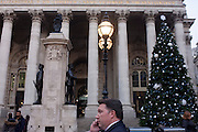 With the Victorian neo-Roman architecture of Royal Exchange and the WW1 memorial and a Christmas treet in the background, a businessman talks on his phone, on 9th December 2016, in the City of London.