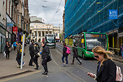 People crossing the road in front of a Nottingham Express Transit (NET) tram on Market Street, Nottingham, Nottinghamshire, United Kingdom. One of the Ecolink buses is driving alongside, which is a zero emissions, electric bus that reduces air and noise pollution in the city. (photo by Andrew Aitchison / In pictures via Getty Images)