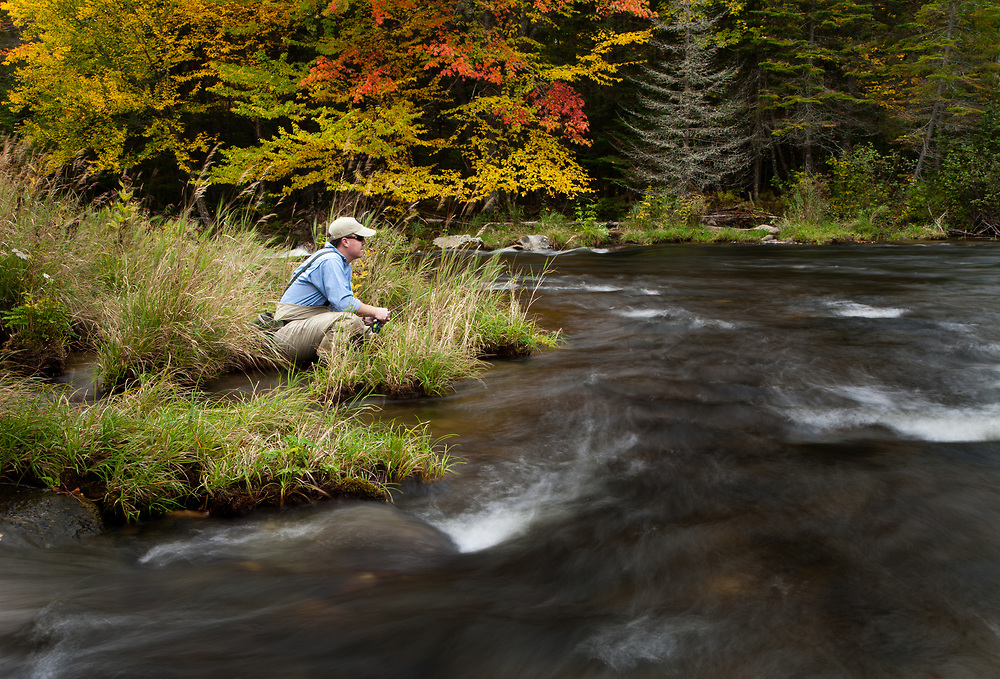 Male angler sits quietly on the stream bank while fly fishing for trout on the upper Connecticut River in northern New Hampshire.