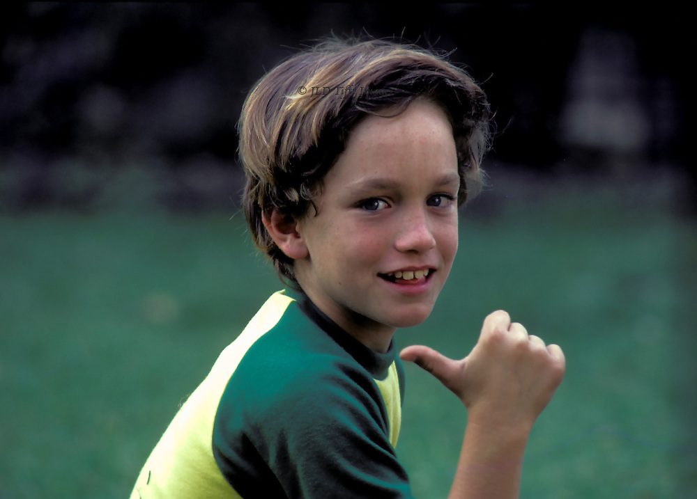 Head and shoulders portrait of a boy aged 10 years, pointing behind him with his thumb, mysterious smile showing new large incisors.  Thick brown straight hair, green and yellow T-shirt, grassy background.