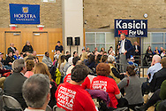 Hempstead, New York, USA. April 4, 2016. JOHN KASICH, Republican presidential candidate and governor of Ohio, speaks at the Town Hall he's hosting at Hofstra University David Mack Student Center in Long Island. Audience includes senior citizens from Long Island AARP (American Association of Retired Persons) wearing red shirts with message 'Does Your Candidate Have A Plan For Social Security?' on back, . The New York primary is April 19, and Kasich is the first of the three GOP presidential candidates to campaign in Nassau and Suffolk Counties, and is in third place in number of delegates won.