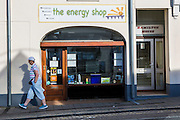 A woman walks past the Wadebridge Renewable Energy Network (WREN) energy shop in Wadebridge, North Cornwall, United Kingdom. The shop is the focal point for WRENs activities which aims to turn the area into the first renewable energy town.