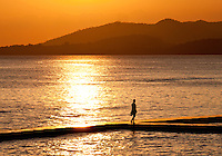 Female figure silhouetted in the setting sun at Puris Bagus in Candidasa, Bali, Indonesia