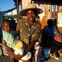 Africa, Botswana, Francistown, Woman and son at bus stop at sunset