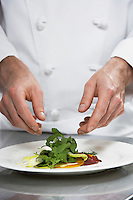 Male chef preparing salad mid section