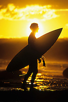 Silhouette of surfer carrying surfboard along beach side view