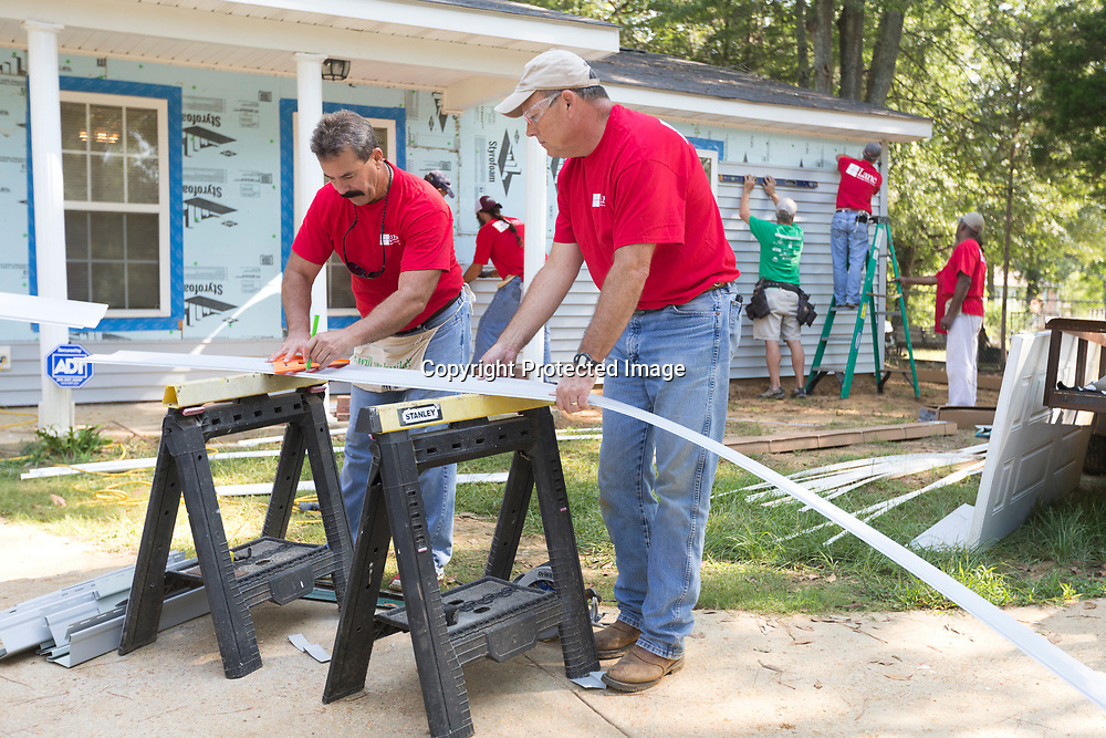 Mike Koon, left, and Bill Collins measure and cut a piece of siding as they and other Lane Furniture employees volunteer their time building a Habitat for Humanity home Friday morning in Verona.