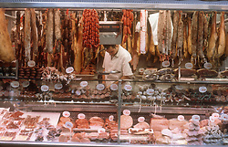 La Boqueria market in Barcelona  stall featuring lots of sausages and cooked meat,