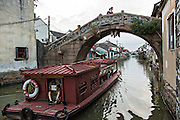 Boat travels along Shantang canal in Suzhou, China.