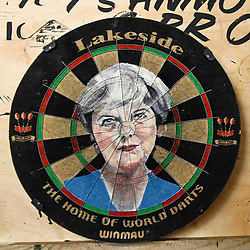 "© Licensed to London News Pictures. 17/08/2018. LONDON, UK. An images of Theresa May painted onto a dartboard by Zara Gaze at ""Letterheads 2018: London Calling"", an international gathering of professional sign writers and lettering artists from over 30 countries.  The event is taking place at the Bargehouse, Oxo Tower Wharf in central London untikl 19 August.  Photo credit: Stephen Chung/LNP"