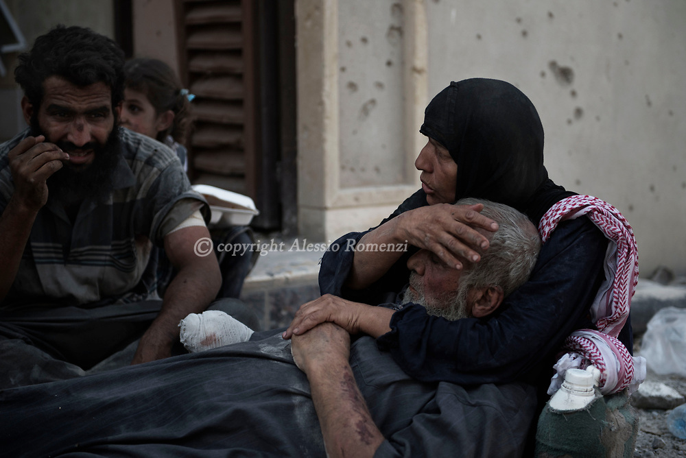 IRAQ, Mosul: An old woman takes care of her wounded husband after they managed to escape the fighting area inside the old city in Mosul. Alessio Romenzi