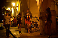 Women leave Tu Candela discotec with foreign tourists near the clock tower in the historic center of Cartagena, Colombia. Tu Candela is a discotec popular among tourists, who go there to drink, dance and to pick up prostitutes. Tu Candela is where the prostitute at the heart of the secret service scandal regularly went to pick up clients.