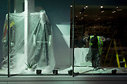 Ten weeks after the UK went into Coronavirus pandemic lockdown, the Office for National Statistics reveal that the total death toll has passed 50,000 covid-19 victims, clothing mannequins in the shop window of a retailer undergoing extensive refurbishment, are covered in a protective layer of plastic, in the City of London, the capital's financial district, on 2nd June 2020, in London, England. The retail industry has taken advantage of quiet roads during lockdown, as an opportunity to have repairs and refurbs caried out in their premises.