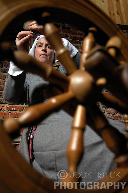 AARSCHOT, BELGIUM - MARCH-14-2007 -  Maris Lowers works at a spinning wheel in the Sint-Rochustoren Tower, a medieval tower that was closed to the public for 600 years. Lowers is a member of the Orde Van De Hagelanders, a group who recreates medieval life and convinced the city of Aarschot to allow them to restore the tower to its medieval glory. (Photo © Jock Fistick)