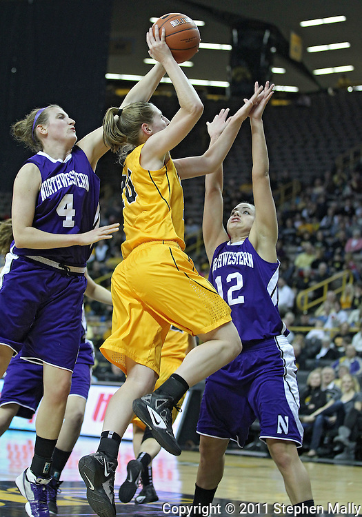 December 30, 2011: Northwestern Wildcats forward Kendall Hackney (4) blocks a shot by Iowa Hawkeyes forward Kelly Krei (20) as Northwestern Wildcats guard Allison Mocchi (12) defends during the NCAA women's basketball game between the Northwestern Wildcats and the Iowa Hawkeyes at Carver-Hawkeye Arena in Iowa City, Iowa on Wednesday, December 30, 2011.
