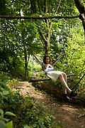 Teenager On Swing In Woods
