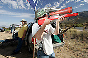 Justin Rogers scans the hillside near Sierra Vista  for undocumented immigrants with his homemade scope setup, while his father William hydrates in the background. Both father and son are members of the Minutemen, a group of volunteers who patrol the US-Mexico border in search of what they call illegal immigrants.