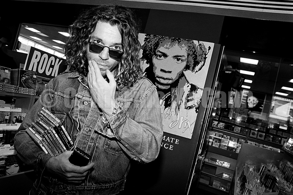 NEW YORK - OCTOBER 1993:  Australian singer songwriter Michael Hutchence (1960-1997) of the rock band INXS, poses for a photo in front of a poster of Jimi Hendrix while shopping for CDs at Tower Records in October 1993 in New York City, New York. (Photo by Catherine McGann).Copyright 2010 Catherine McGann