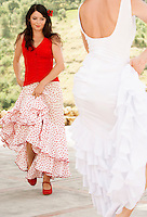 Two women flamenco dancing outdoors.