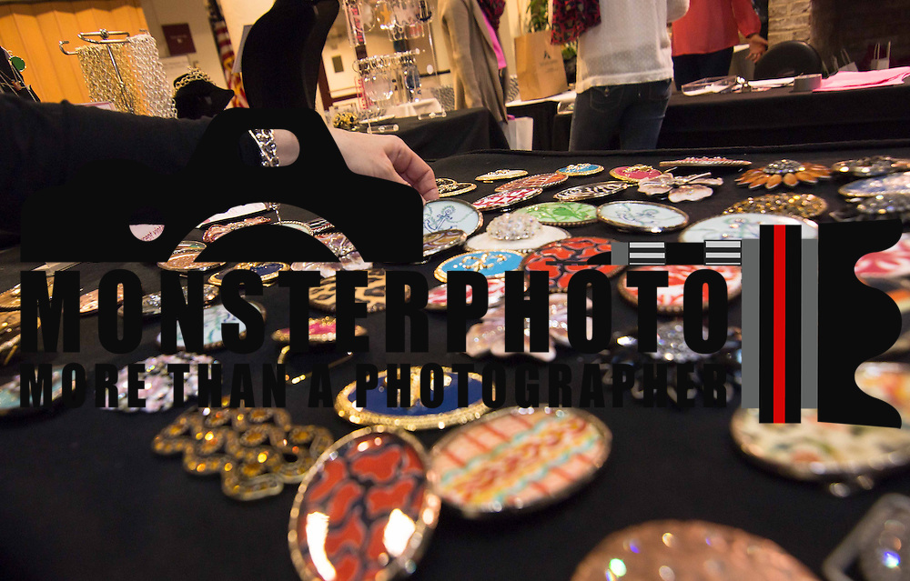 The hand of Liza Balaci (LEFT) picks up a belt buckle at the BTG Buckled To Go booth during the 3rd Annual Guilty Girls Warehouse Sale Friday, Feb. 06, 2015 at University of Delaware's Arsht Hall in Wilmington, DE.