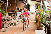 "10 JULY 2011 - AMPHAWA, SAMUT SONGKRAM, THAILAND:   Boys in Amphawa, Thailand, ride a bike on the boardwalk along the town's main canal. The Thai countryside south of Bangkok is crisscrossed with canals, some large enough to accommodate small commercial boats and small barges, some barely large enough for a small canoe. People who live near the canals use them for everything from domestic water to transportation and fishing. Some, like the canals in Amphawa and nearby Damnoensaduak (also spelled Damnoen Saduak) are also relatively famous for their ""floating markets"" where vendors set up their canoes and boats as floating shops.      PHOTO BY JACK KURTZ"