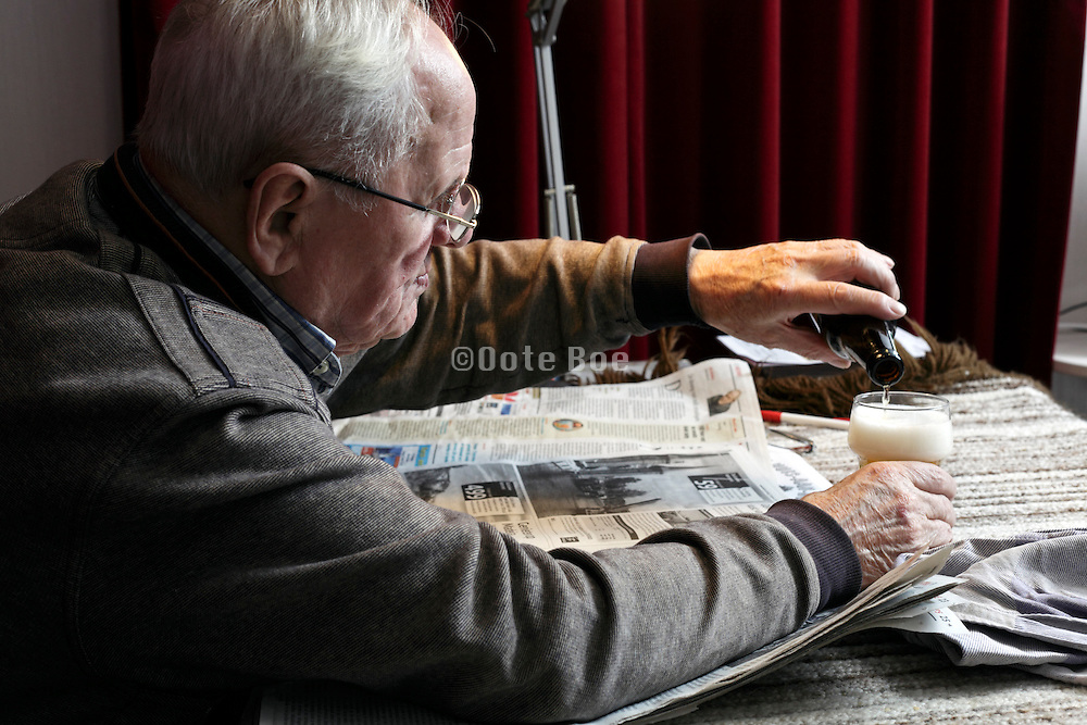 portrait of 89 year old man reading the newspaper and drinking a beer