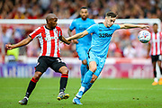 Derby County forward Tom Lawrence (10) tussles with Brentford midfielder Kamohelo Mokotjo (12) during the EFL Sky Bet Championship match between Brentford and Derby County at Griffin Park, London, England on 31 August 2019.