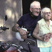 Elderly white Caucasian couple living just above the poverty level in back yard of home standing next to motor cycle they have been married 50 years, Welaka, FL Intimacy and sexual interactions are important to us throughout our lives.
