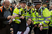 A legal observer puts an information sheet into the hand of Prof. Colin Davis, a Bristol University PhD in human cognition and an activist with Extinction Rebellion as he's arrested during the London protest about climate change in a blocked-off Oxford Circus , on 17th April 2019, in London, England.