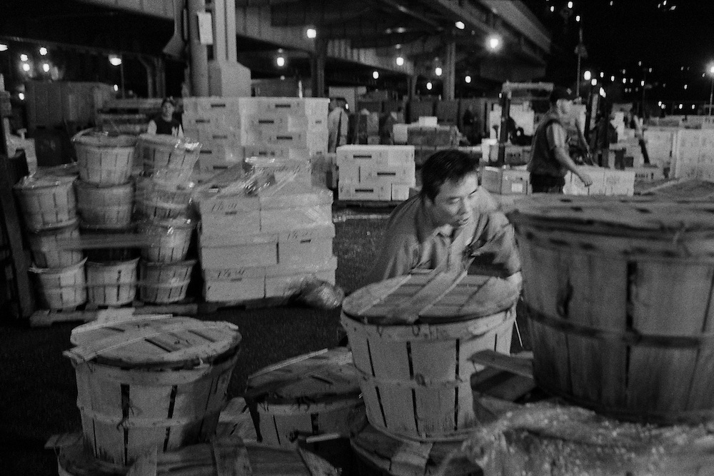 This man is packing and moving bushels of seafood. The hook in his hand is used to grab the bushels and drag them along the ground. Most people working in the market had a similar hook. The Fulton Street Fish Market operated in this location near the Brooklyn Bridge for 183 years until it was relocated to the Bronx in 2005.