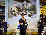 "25 OCTOBER 2017 - BANGKOK, THAILAND: A man in a Bangkok shopping mall takes a ""selfie"" in front of art work of the King during the funeral for Bhumibol Adulyadej, the Late King of Thailand. He died in October 2016 and was cremated during an ornate five day funeral on 26 October 2017. He reigned for 70 years and was Thailand's longest serving monarch.         PHOTO BY JACK KURTZ"