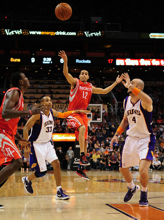 Feb. 9, 2012; Phoenix, AZ, USA; Houston Rockets guard Kevin Martin (12) makes a pass over Phoenix Suns forward Grant Hill (33) during the first half at the US Airways Center. The Rockets defeated the Suns 96-89. Mandatory Credit: Jennifer Stewart-US PRESSWIRE.