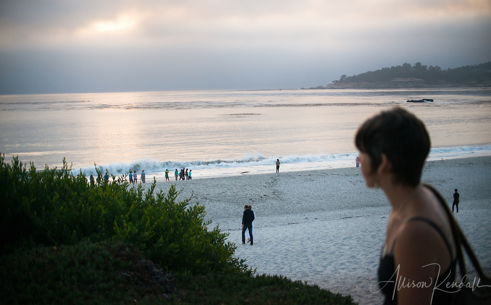 People gather on the sand at the water's edge, one quiet sunset evening in Carmel-by-the-Sea