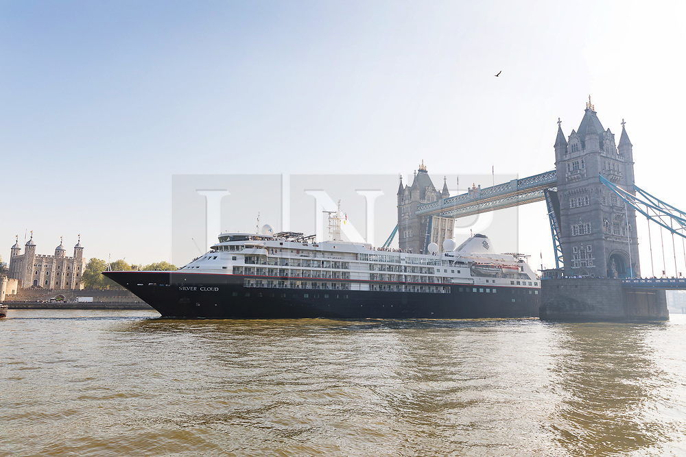 © Licensed to London News Pictures. 08/05/2018. London, UK. The first cruise ship of the year arrives under Tower Bridge in London, marking the start of the summer cruise ship season. Passengers aboard the huge, 157 metre long cruise ship, Silver Cloud cheered as she arrived under Tower Bridge during hot, sunny weather this morning. Photo credit: Vickie Flores/LNP