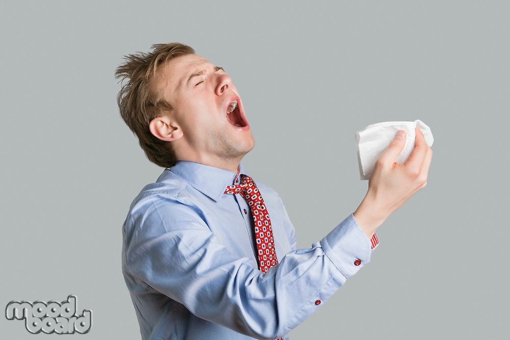 Young man sneezing with open mouth and handkerchief over colored background