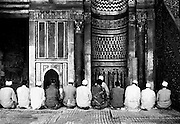 Seen from the back, a neat row of 11 men with one more leader in front of them is seated on their heels in the course of doing their prayers.  The qibla and wall in front of them is elaborately inlaid with multicolored marble discernible despite the monochromatic image.  The mosque dates from 1415-1422.