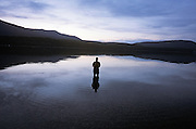person standing alone in shallow water. Glacier National Park Montana USA
