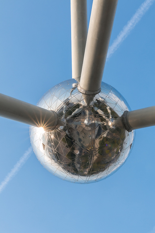 The Atomium is a building in Brussels originally constructed for Expo 58, the 1958 Brussels World's Fair. Designed by the engineer Andr&eacute; Waterkeyn and architects Andr&eacute; and Jean Polak,[1] it stands 102 m (335 ft) tall. Its nine 18 m (59 ft) diameter stainless steel clad spheres are connected so that the whole forms the shape of a unit cell of an iron crystal magnified 165 billion times.<br /> <br /> Tubes connect the spheres along the 12 edges of the cube and all eight vertices to the centre. They enclose escalators and a lift to allow access to the five habitable spheres which contain exhibit halls and other public spaces. The top sphere provides a panoramic view of Brussels. CNN named it Europe's most bizarre building.
