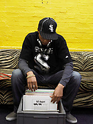 Young man sat on zebra print couch looking through a box of vinyl records.
