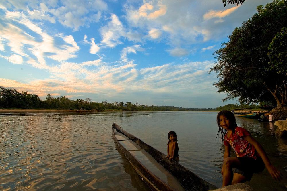 Girls play around a canoe on the Napo river, Amazon Ecuador