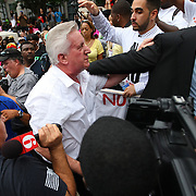 "A George Zimmerman supporter (white shirt) is escorted out of the crowd during the No Justice No Peace- ""March Against Gun Violence""  walk from Lake Eola in downtown Orlando, to the Orange County Courthouse on Wednesday, July 17, 2013. The man was walking around with a sign that said Zimmerman was not guilty. (AP Photo/Alex Menendez)"